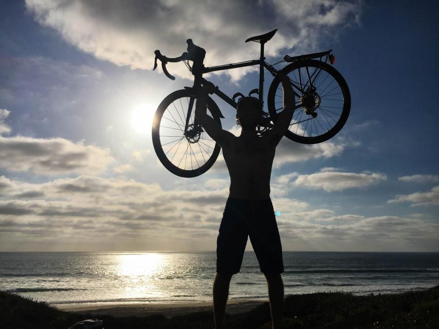 Colin holding his bike in the air at sunset after reaching San Diego